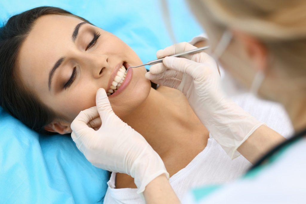 Пациент стоматологии после имплантации зубов на стоматологическом осмотре врача